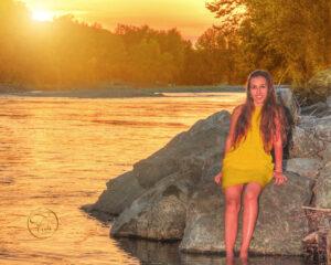 séance photo sur les rives du gave de Pau avec le photographe Fabien Ferrère à Pau. le modèle, vêtue d'une robe jaune, baigne dans un coucher de soleil et dans le gave de Pau