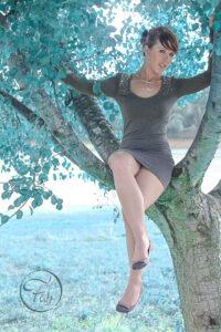 séance photo en extérieur sur un arbre près du lac de Serres-Castet non loin de Pau. fille en robe grise avec Fabien Ferrère photographe de mode et de portrait à Pau et autour de Pau