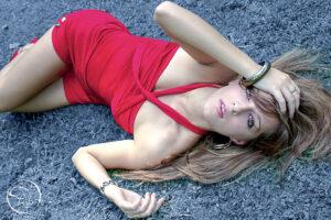 séance photo mode dans l'herbe bleue d'une pelouse d'un jardin public de Pau. Le modèle allongée sur l'herbe porte un ensemble rouge. Shooting avec Fabien Photographe de mode et de portrait à Pau