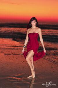 portrait à la plage sur la côte atlantique dans le Pays Basque à ilbarritz au couché su soleil par le photographe Fabien Ferrère. Le modèle porte une robe rouge bordeaux