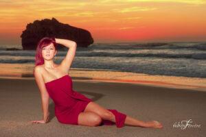 portrait photo sur la plage d'Ilbarritz sur la côte Atlantique dans le pays Basque. le modèle photographiée par Fabien Ferrère porte une robe rouge bordeaux et est allongée sur le sable